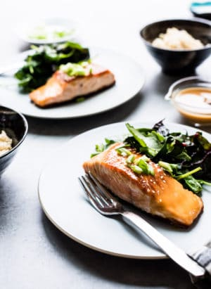 Miso Maple Glazed Salmon served on a white plate alongside a salad of wilted greens.