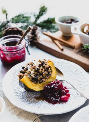 Wedge of Baked Oatmeal Stuffed Acorn Squash on a white plate served with cranberry sauce on the side.