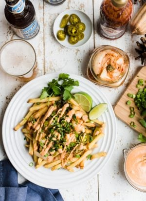 Dig in to spicy Kimchi Fries! These savory bites are spicy, tangy, crunchy and perfectly paired with a Belgian style wheat beer, and guaranteed to disappear at your next party! #pintsandplates #ad