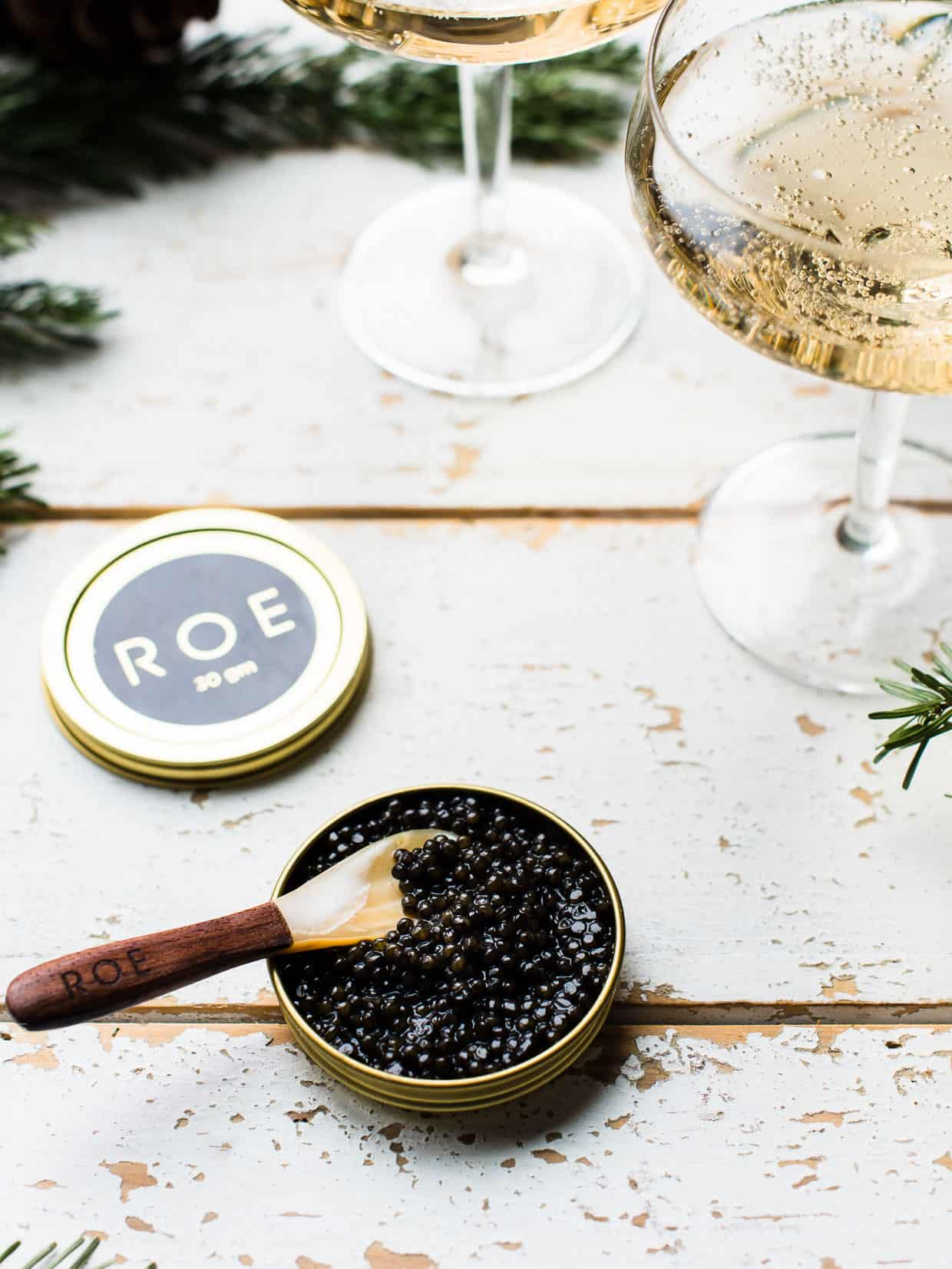 A small container of ROE Caviar with a spoon on a chippy wooden counter top.