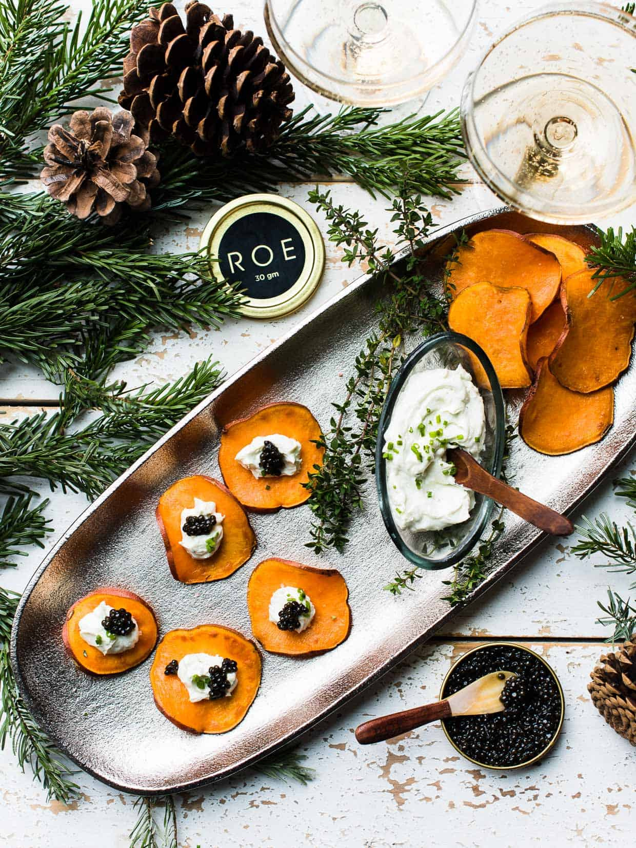 Sweet Potato Chips with Whipped Goat Cheese and Caviar on a serving tray surrounded by additional caviar, goat cheese, and festive pine boughs.