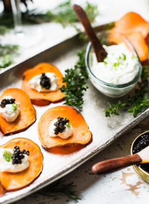Sweet Potato Chips with Whipped Goat Cheese and Caviar on a serving tray with additional whipped goat cheese alongside.