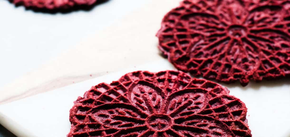 Red Velvet Pizzelle on a marble surface.