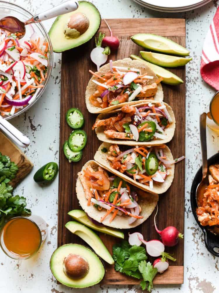 Chipotle Chicken Tacos on a wooden board served with Jicama Slaw.