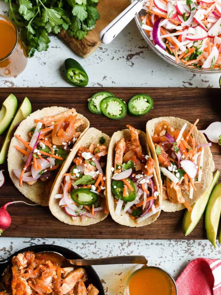Chicken tacos on a wooden board.