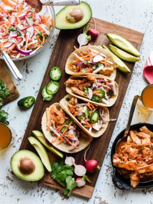 Chipotle Chicken Tacos with Jicama Slaw on a wooden board with avocados, jalapeños and radishes.