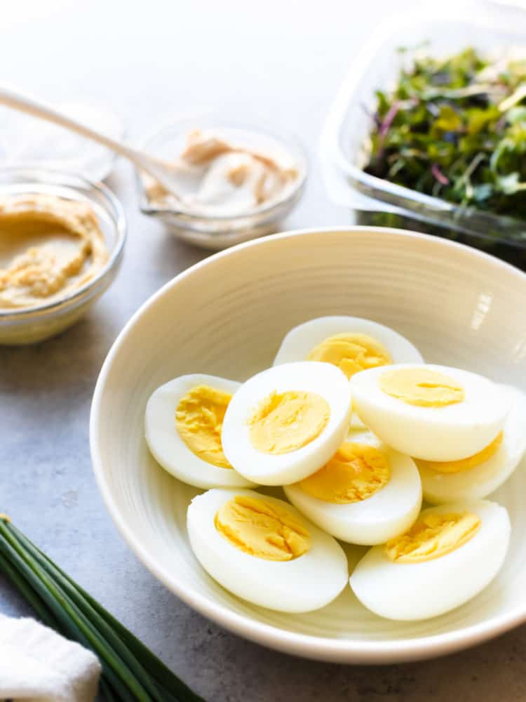 Sliced hard-boiled eggs in a bowl for Hummus and Tahini Egg Salad.