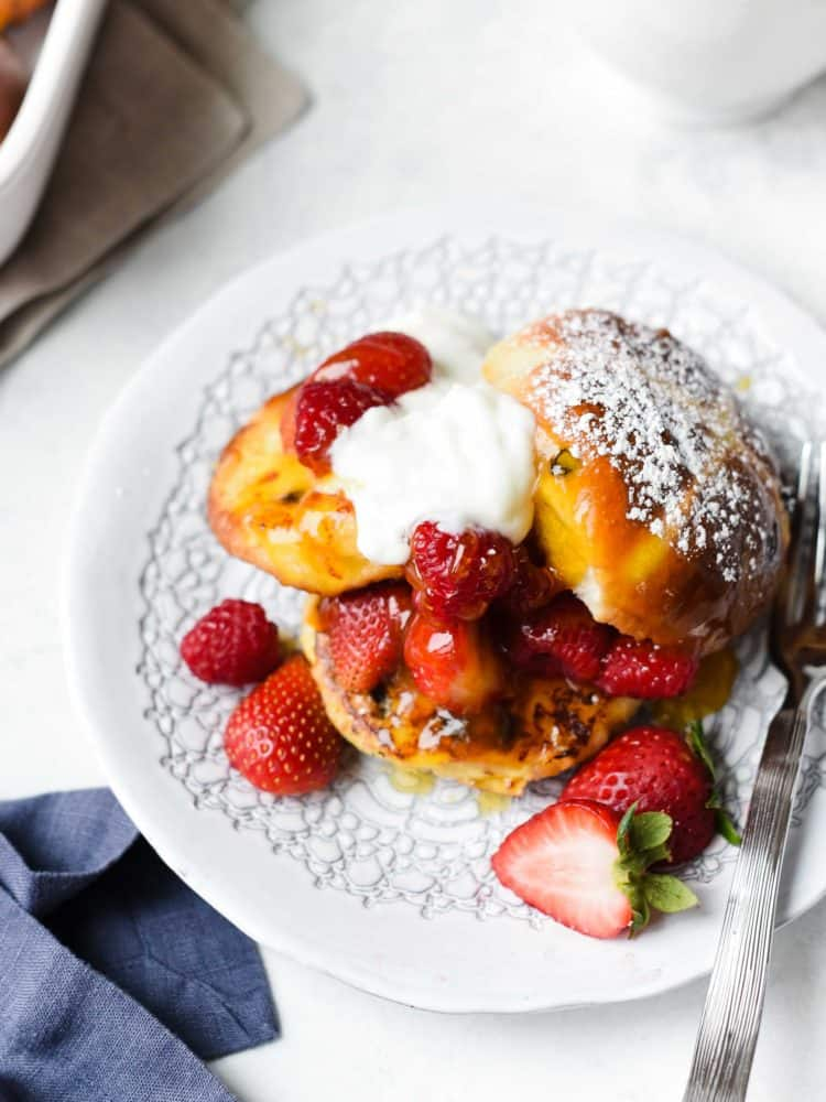 Hot Cross Bun Pain Perdu with fresh berries and cream on a white plate.