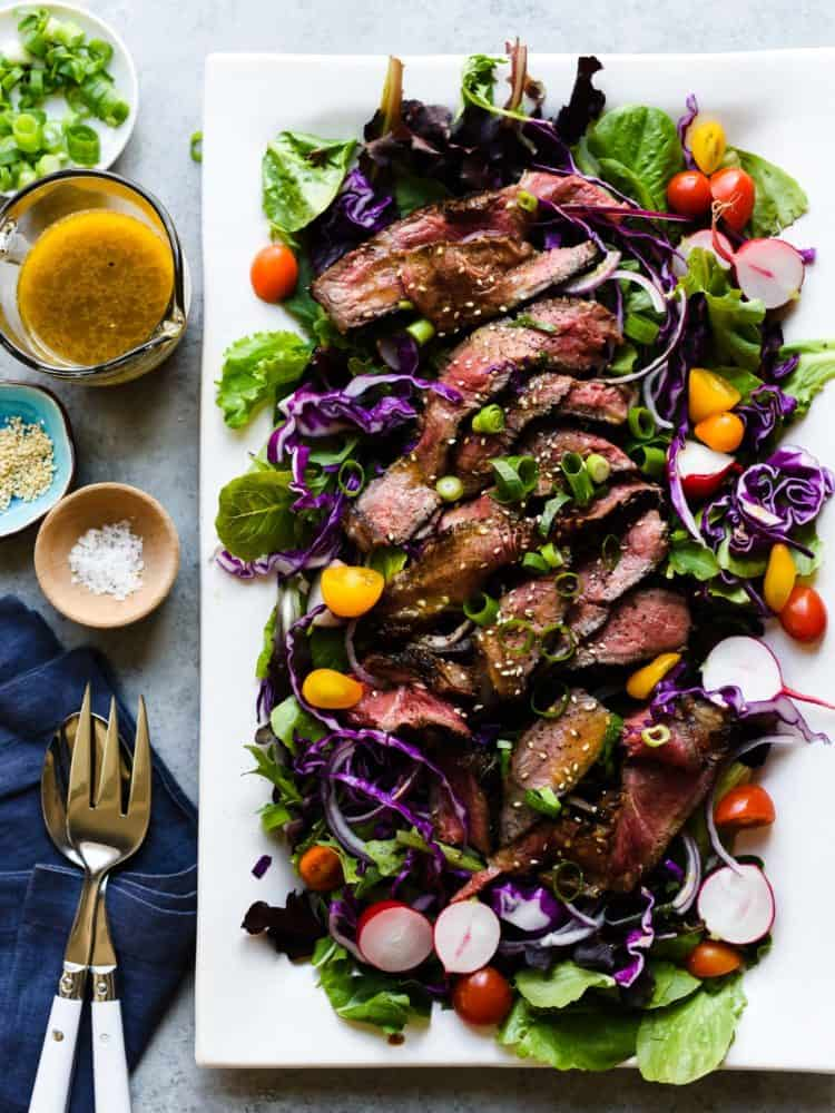 A juicy Miso-Marinated Steak Salad with a Miso-Ginger Dressing on a white platter.