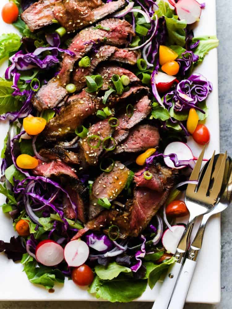 A Miso-Marinated Steak Salad with a Miso-Ginger Dressing on a white, rectangular serving platter.