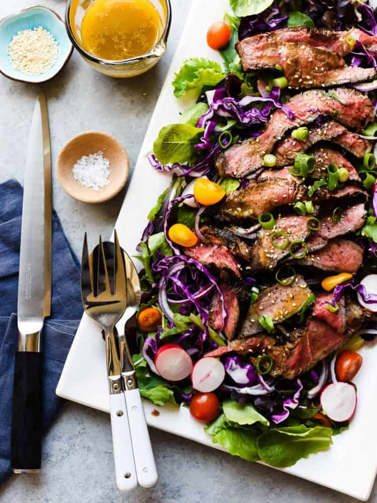 A Miso-Marinated Steak Salad with a Miso-Ginger Dressing on a white platter.