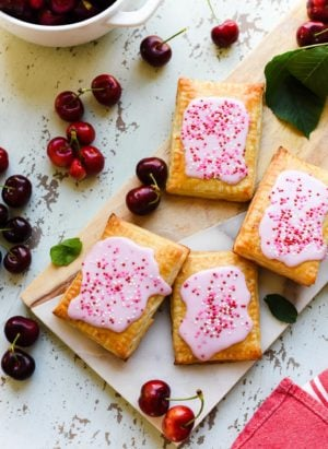 Homemade Cherry Pop Tarts on a wood and marble serving board with fresh cherries.