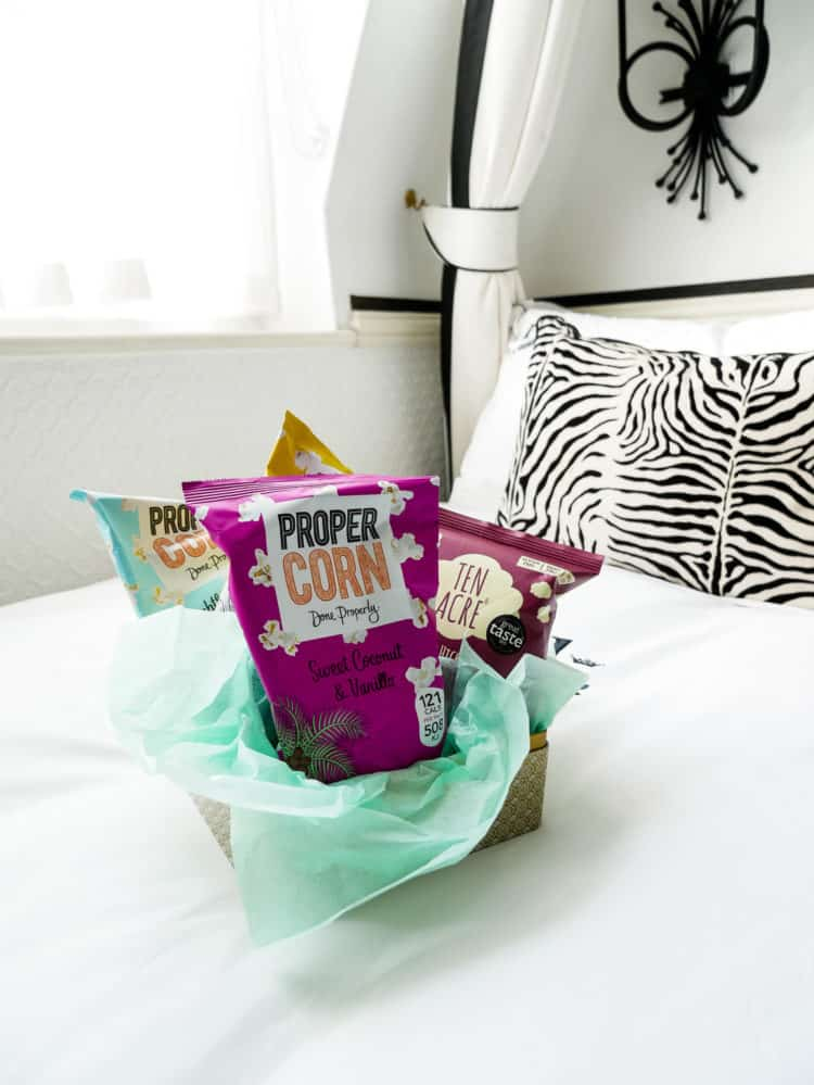 Bags of popcorn snacks on a white hotel bed.