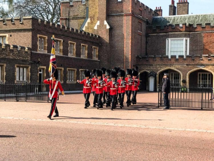 British Royal Guard marching in front of a brick palace.
