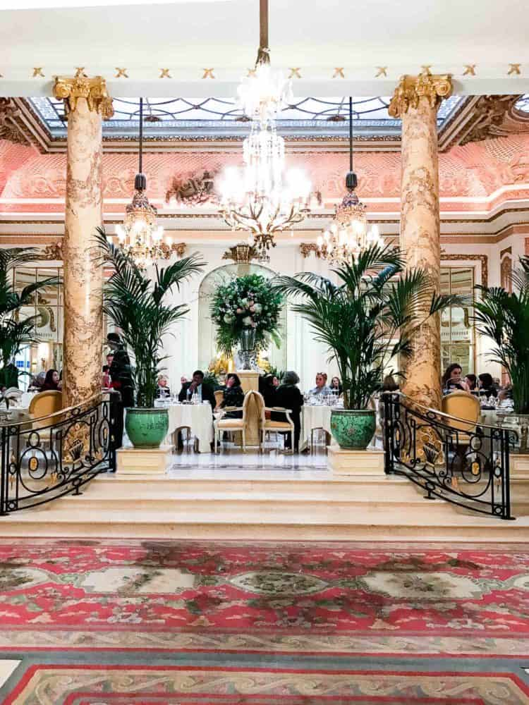 An interior shot of the Ritz in London with pink Oriental rugs, pink marble, ornate chandeliers, and large green potted plants.