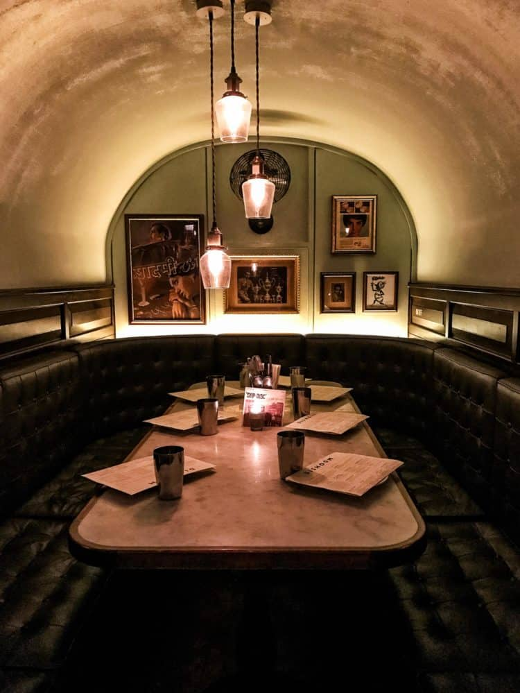 Dark and cozy restaurant booth under a small arch set for 6 people.