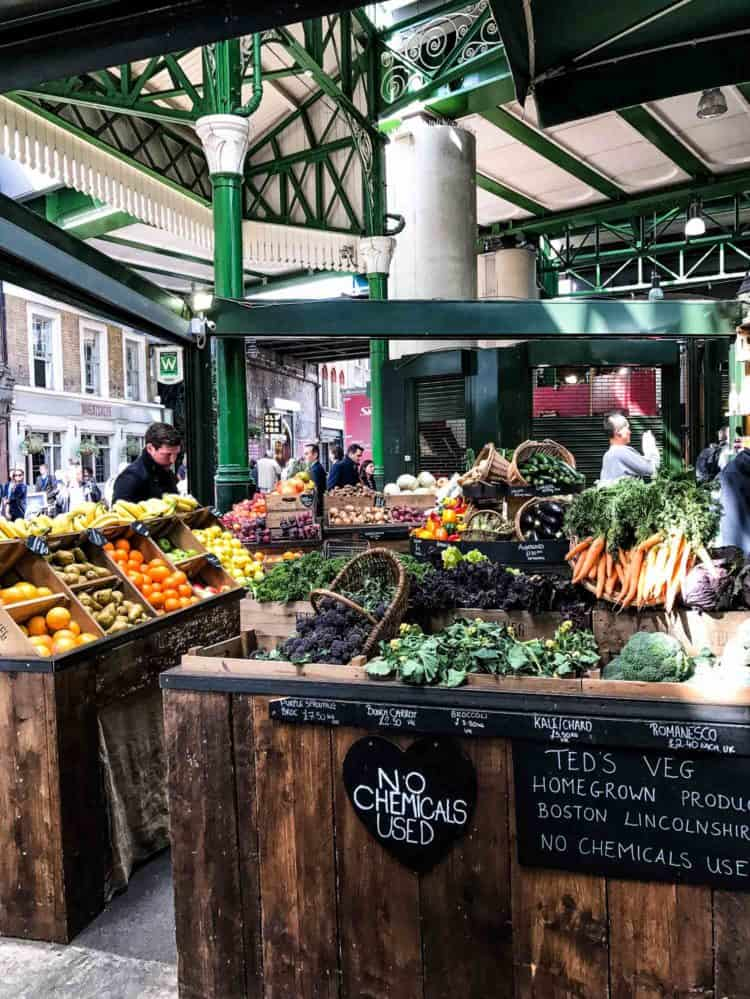 Fresh fruits and vegetables on display on rustic wooden displays at Borough Market in London.
