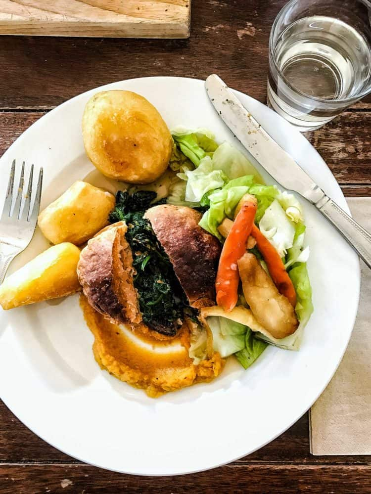 Sunday roast with potatoes, greens, salad, and a roll, served on a white plate.