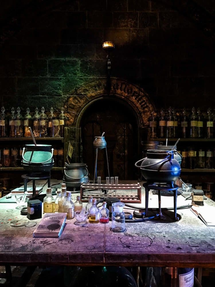 Test tubes, caldrons, and bottles of chemicals in a dark, stone lab in the Potions Room at Warner Bros. Studio Tour.