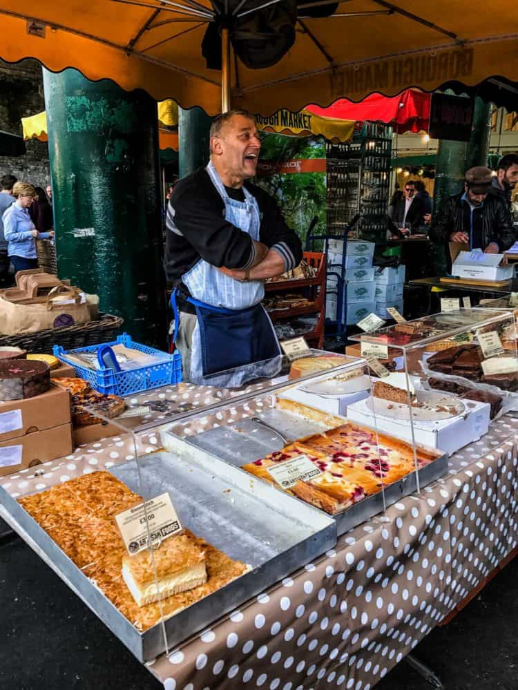 Food stall vendor standing behind pastries at the Borough Market in London.