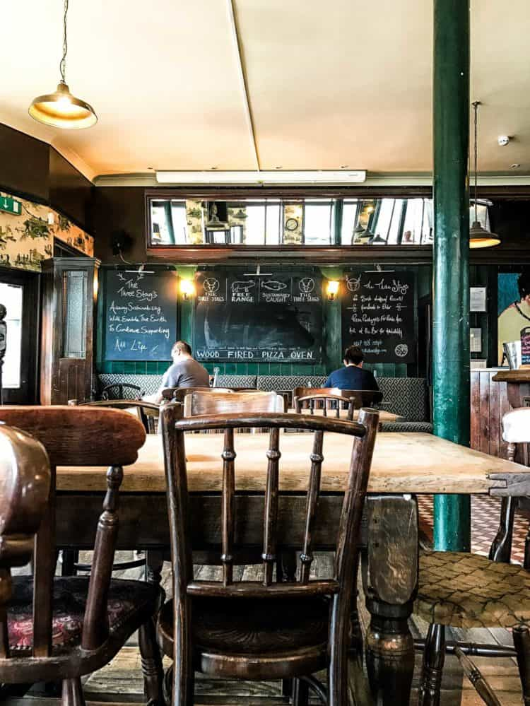 Bright and rustic pub with mixed wooden chairs, chalkboards, and hunter green accents.
