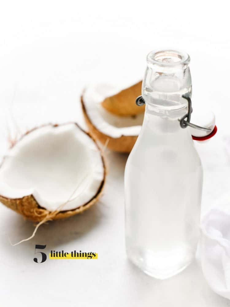 Glass bottle of homemade coconut water and large pieces of coconut