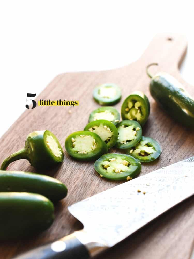 Sliced jalapenos on a wooden cutting board with a chef's knife.