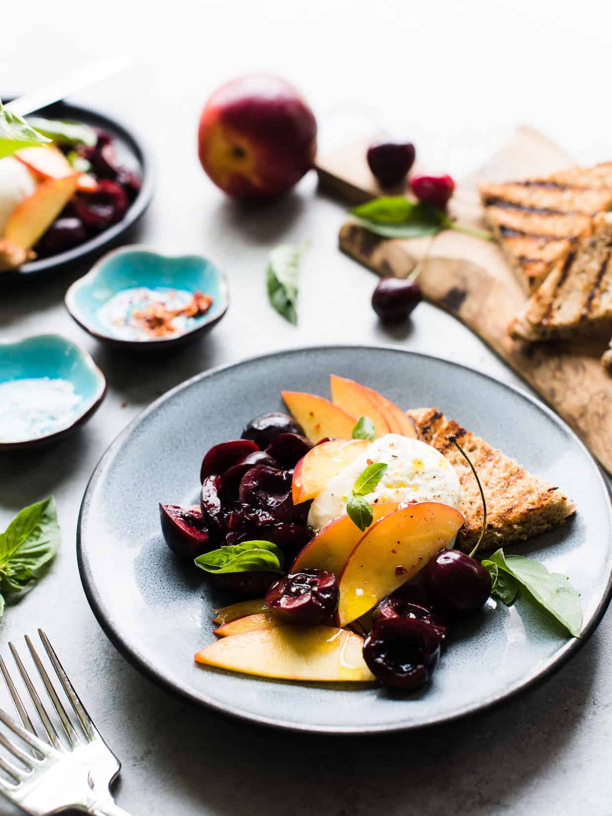 Summer stone fruit, fresh basil, and creamy burrata dressed in a zingy balsamic vinegar and olive oil is the perfect summer appetizer! I used nectarines and cherries, but this will work for any stone fruit you like – try it with plums, peaches, and apricots, too!