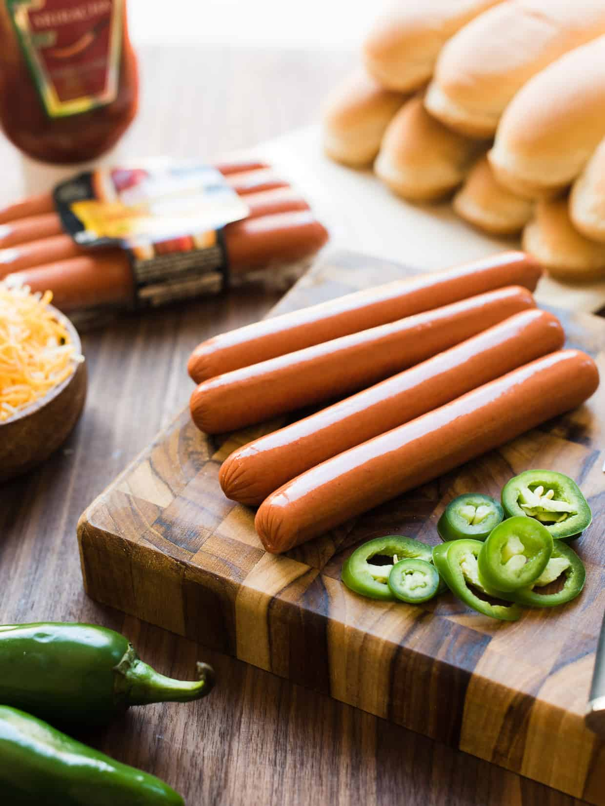 Hot dogs, buns, cheese, jalapeños, and Sriracha ketchup on a wooden board.