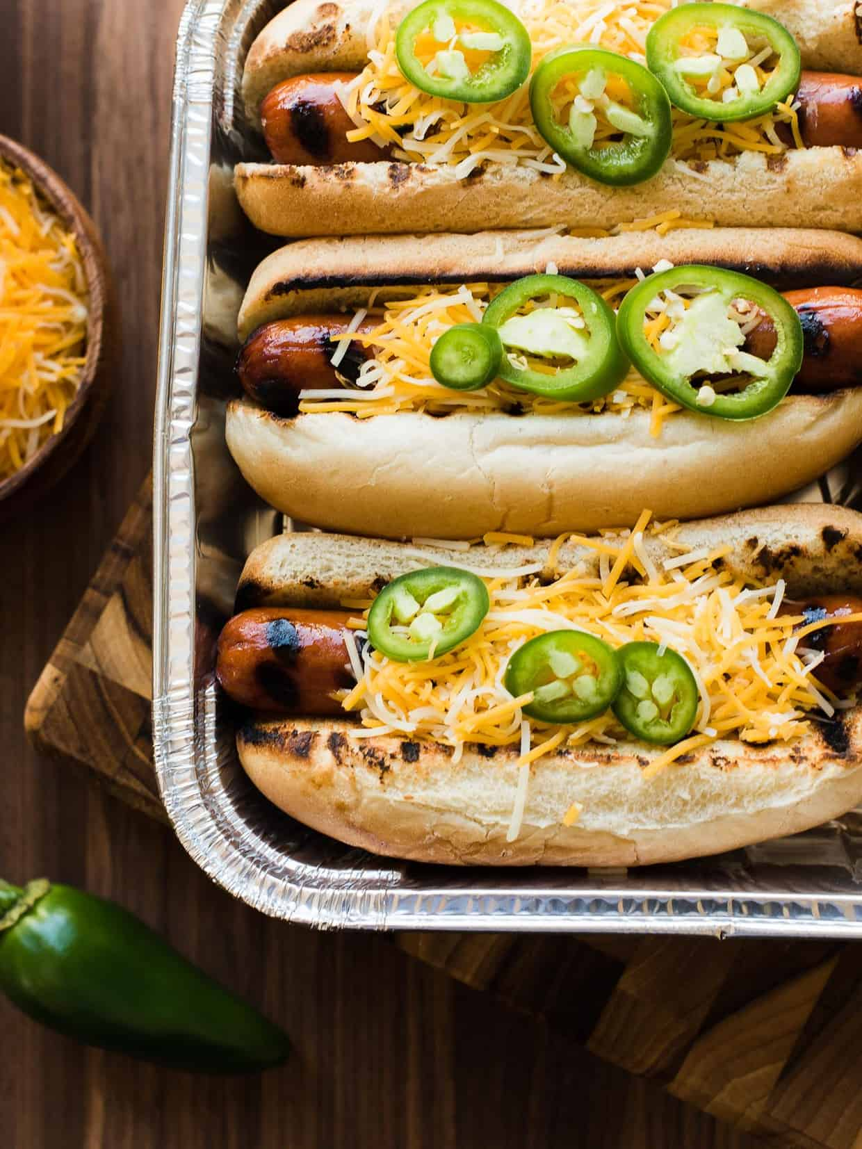 Sriracha Hot Dogs in buns with cheese and jalapeños.