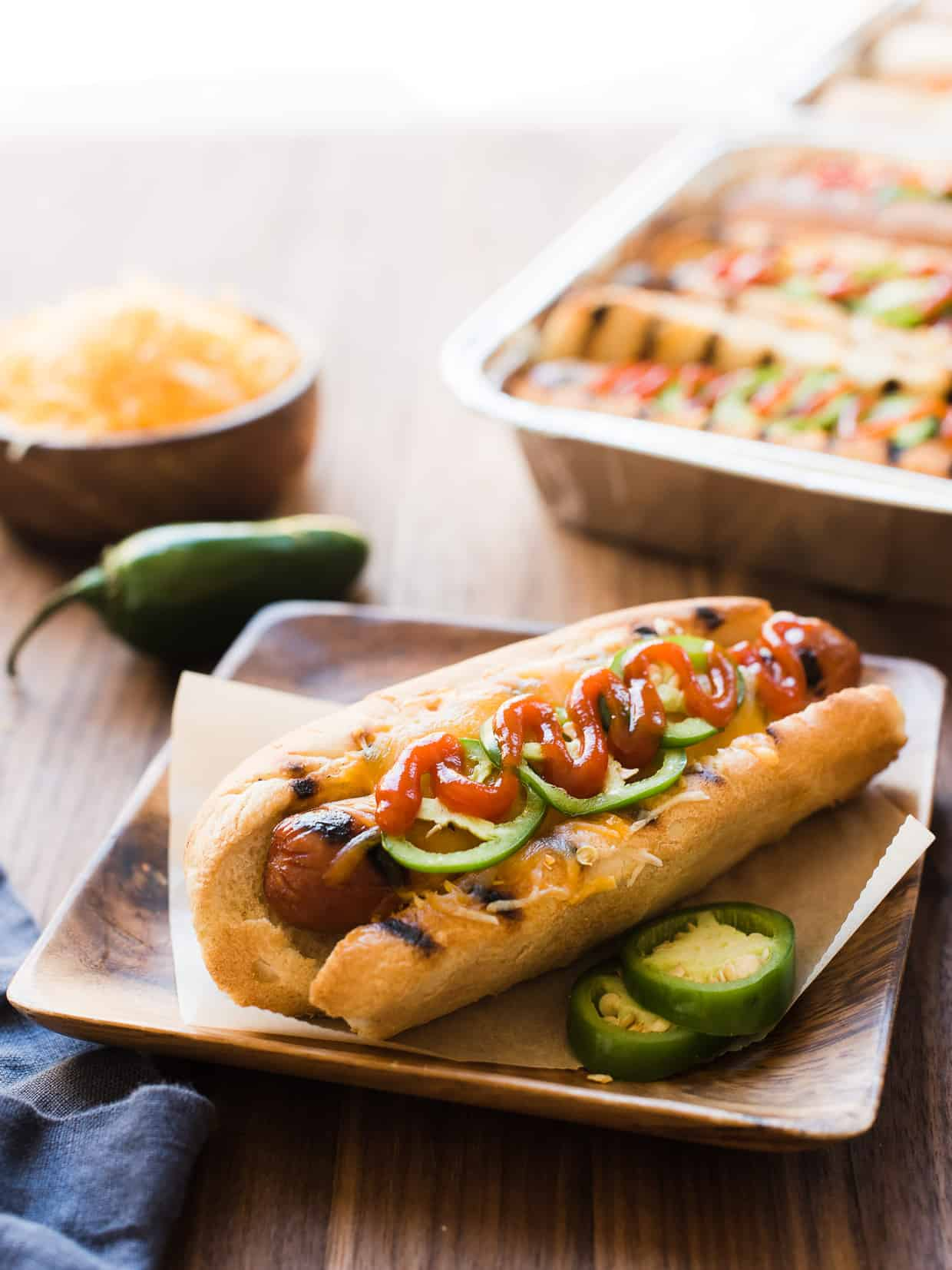 Sriracha Hot Dogs in a bun with cheese and jalapeños.
