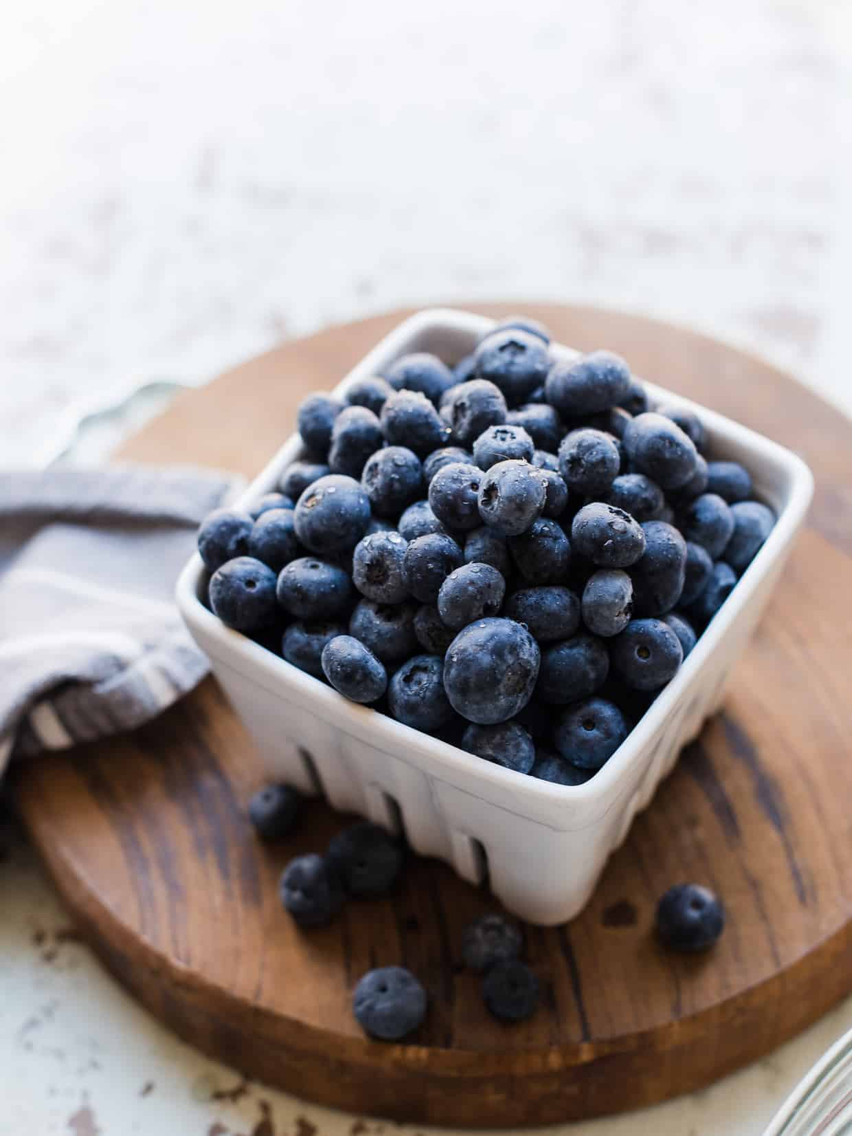 Fresh blueberries in a white basket on a wooden cutting board.