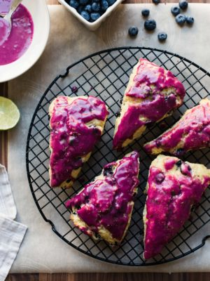Blueberry Goat Cheese Scones with fuchsia blueberry glaze on a cooling rack.