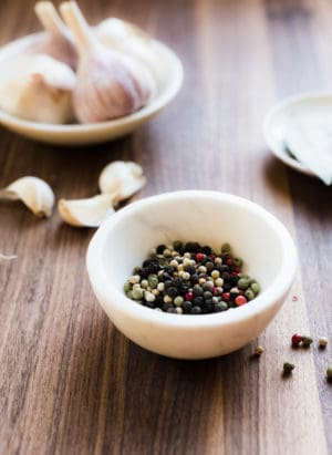 Multi-colored peppercorns in a small white marble bowl with garlic in the background.