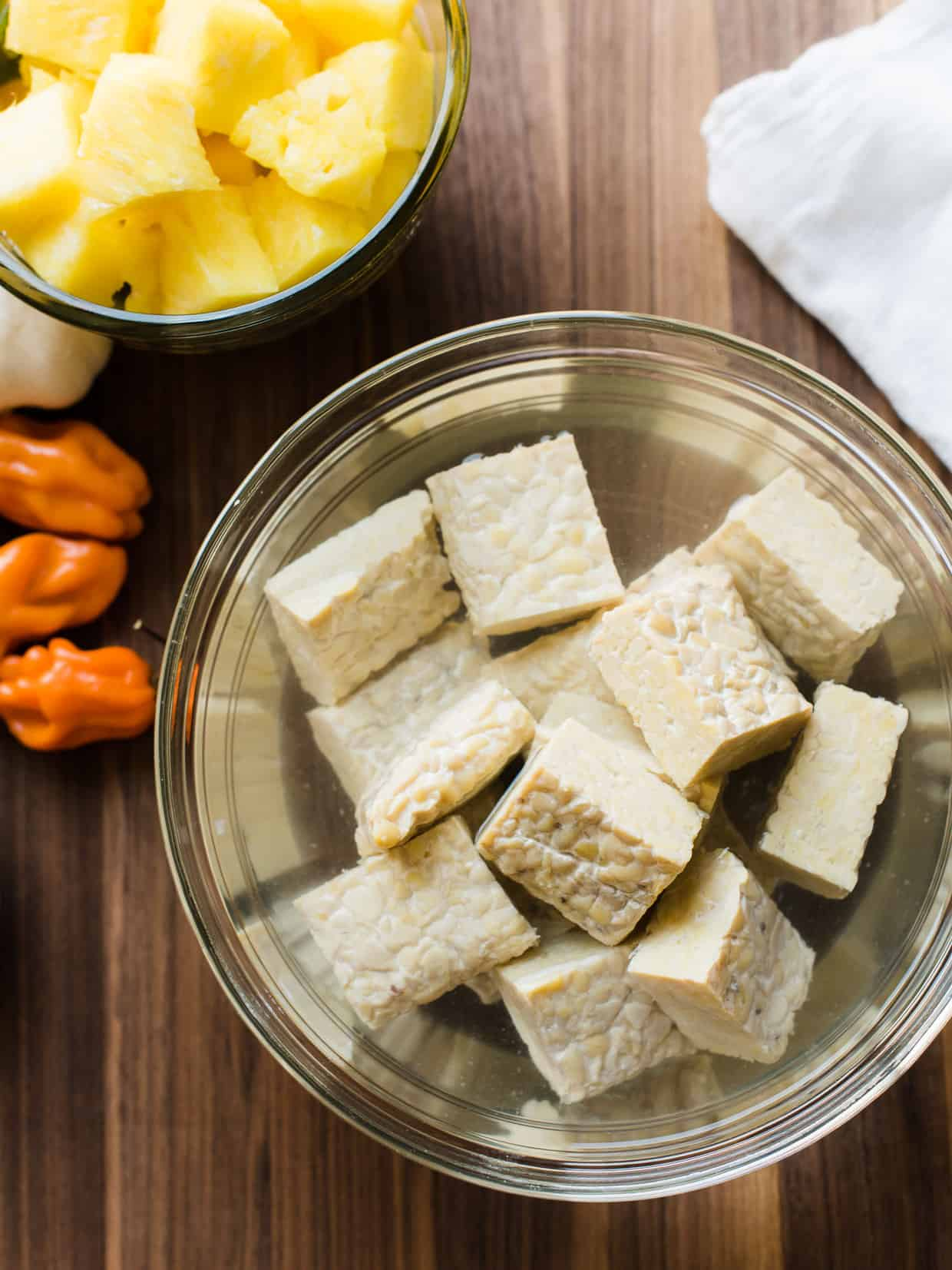 Cubes of tempeh soaking in a glass bowl to make Grilled Tempeh and Vegetable Skewers.