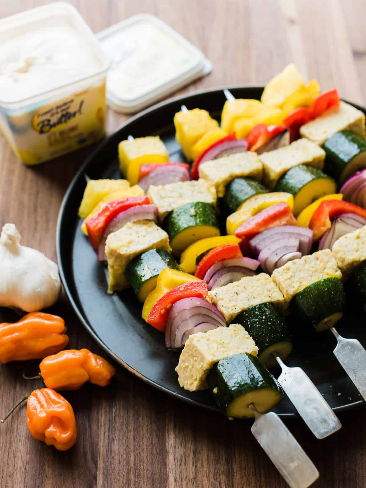 Grilled vegetable skewers with pineapple on a dark plate.