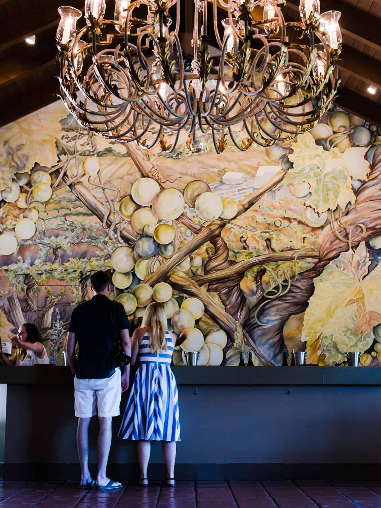 A man and a woman standing in front of a large mural under a large chandelier.