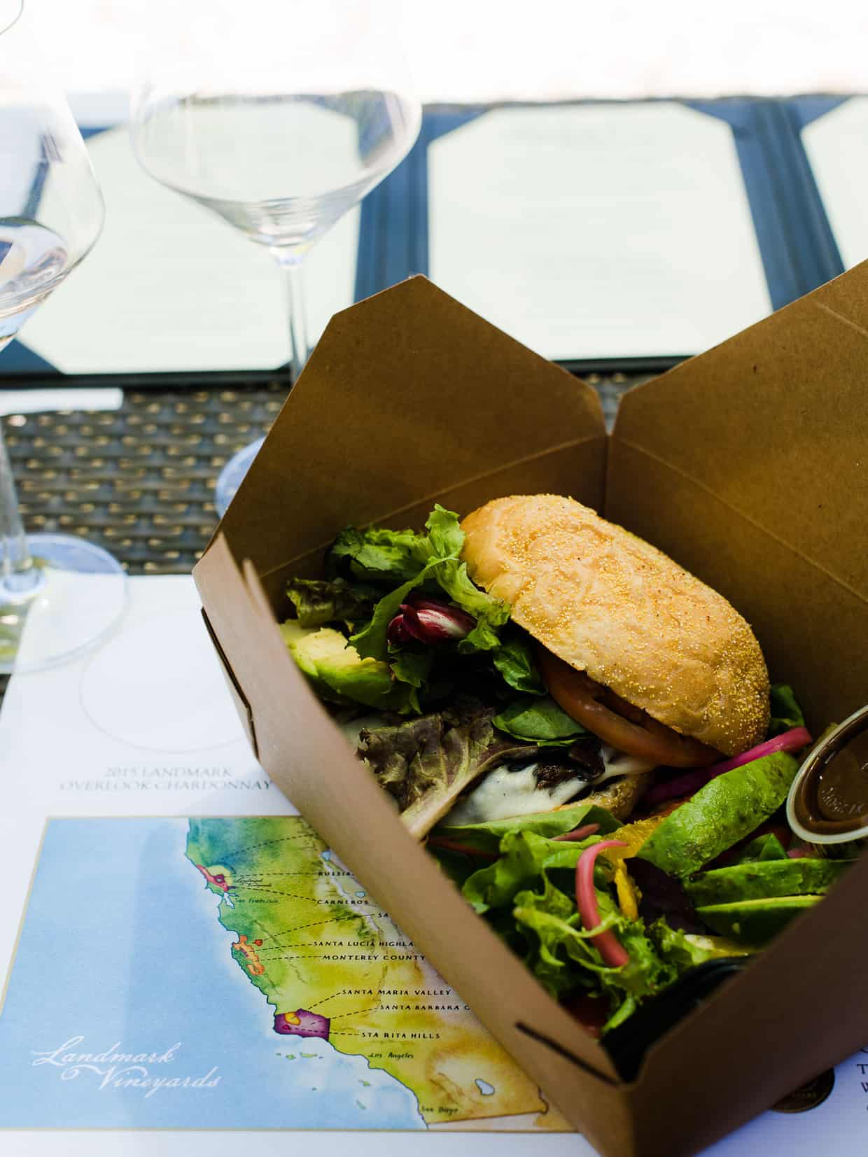 A portobello mushroom burger in a cardboard takeout box.