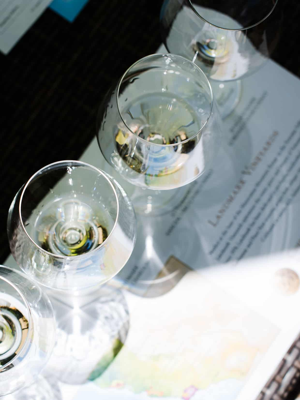 Top down view of 4 wine glasses with white wine at a wine tasting.