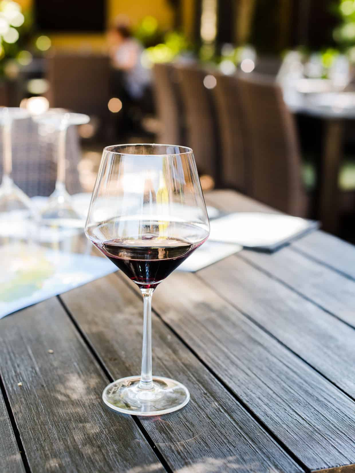 A glass of red wine with tables and chairs in the background.