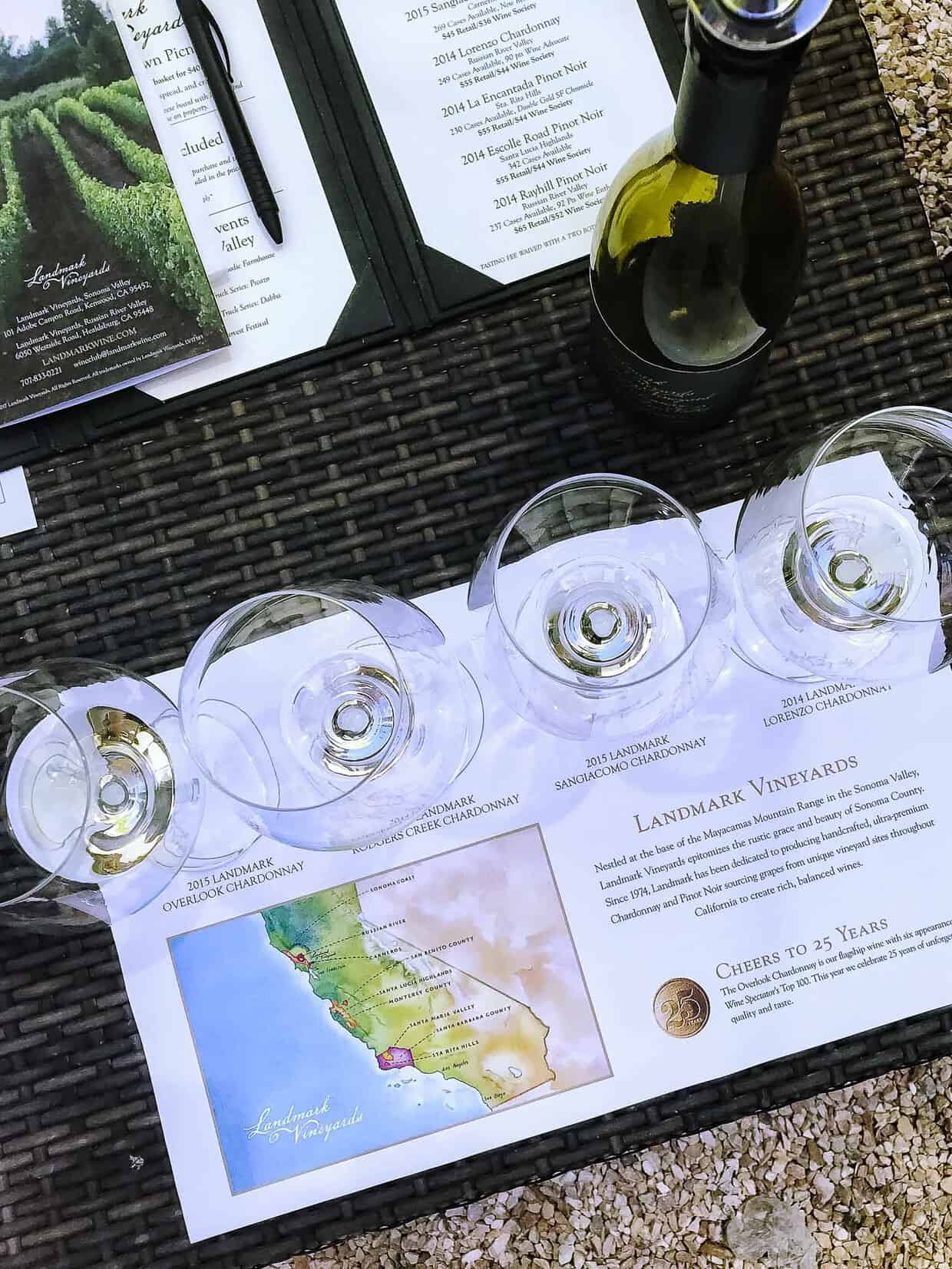 Top down view of 4 wine glasses on a wicker table at a wine tasting.