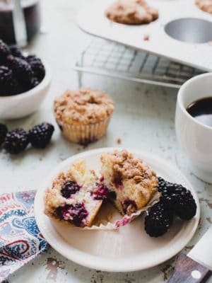 blackberry yogurt muffins cut in half on plate