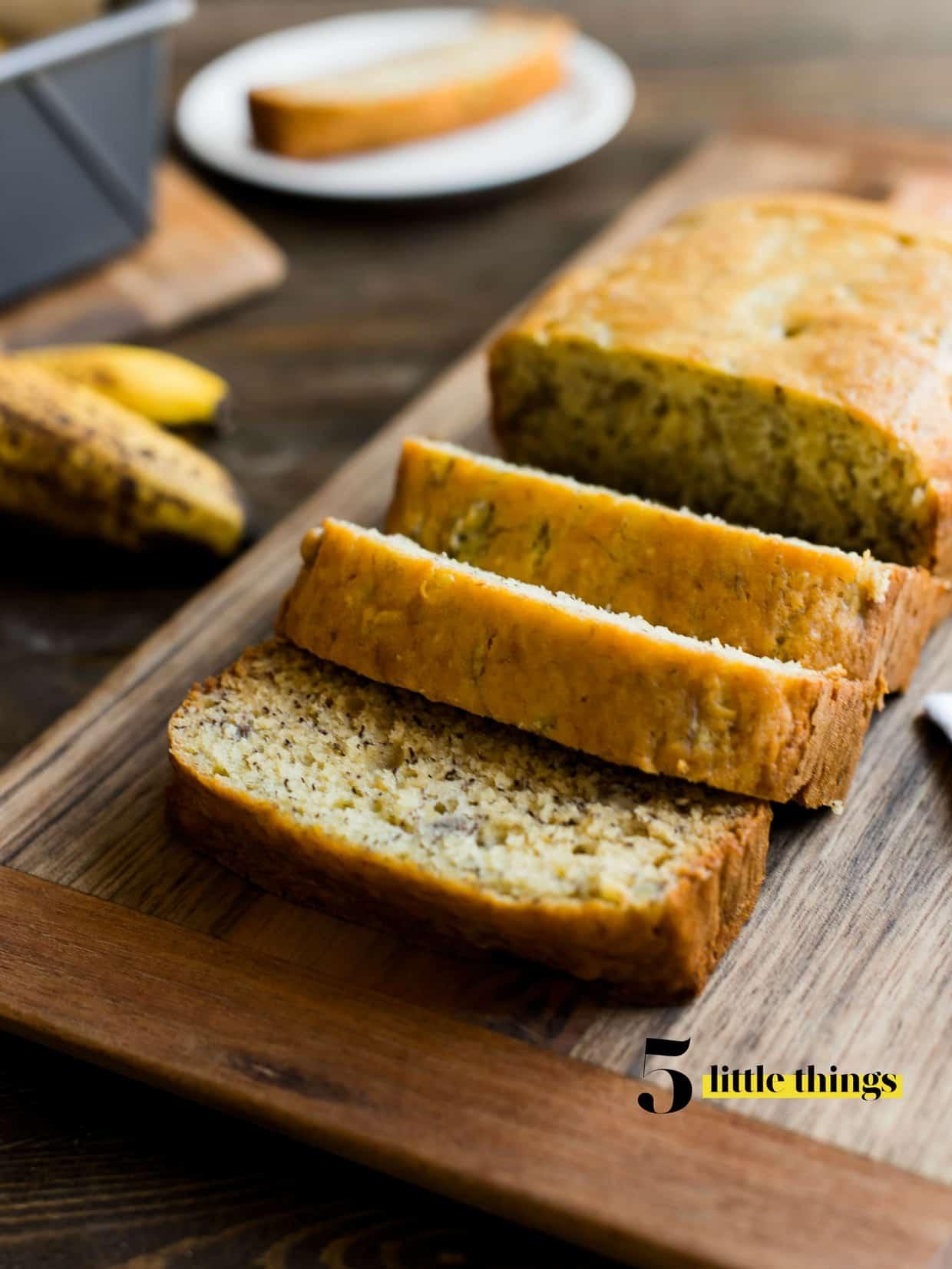 Banana bread sliced on a cutting board.