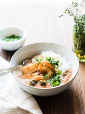 A bowl of homemade seafood gumbo on a wooden surface.