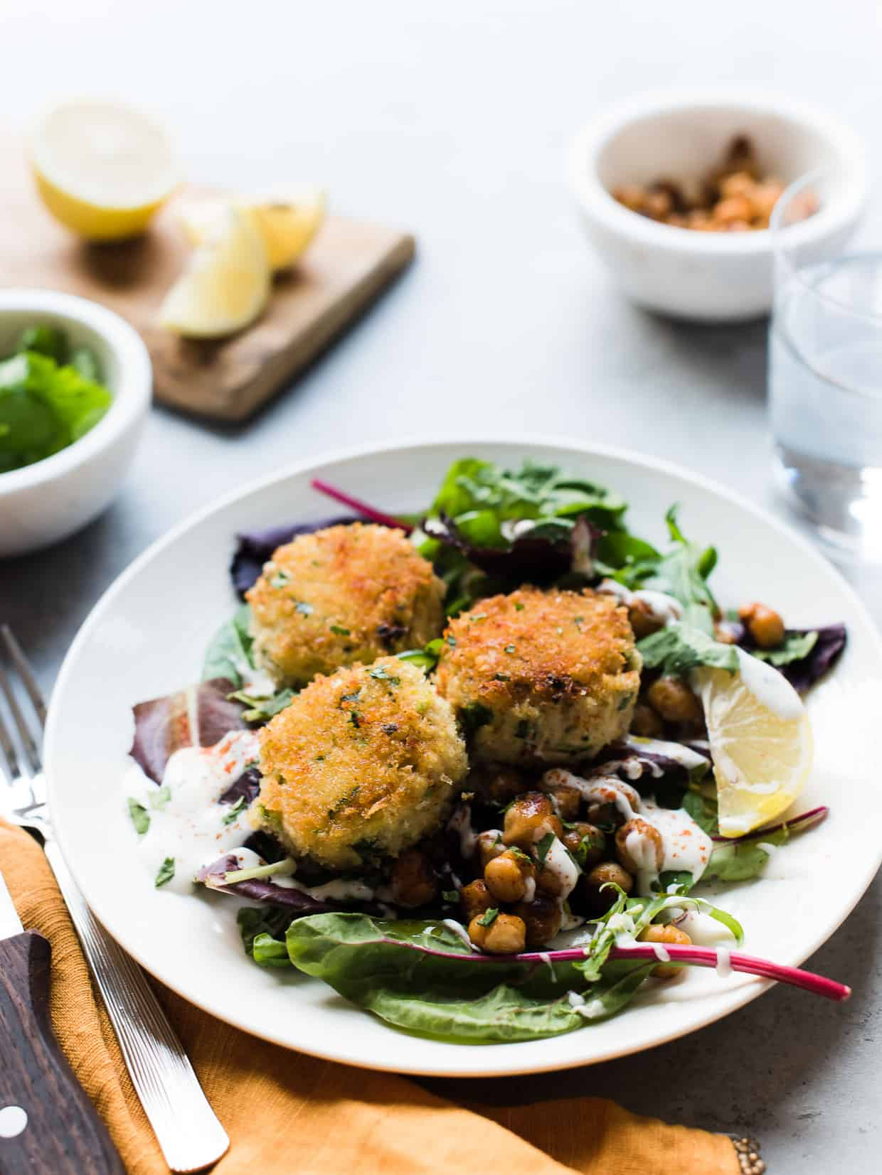 Chickpea Crab Cakes served on top of a fresh green salad.