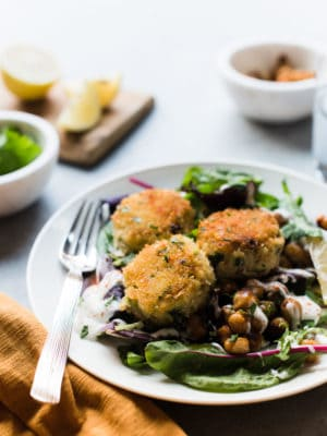 Chickpea crab cakes served on a salad with toasted chickpeas.