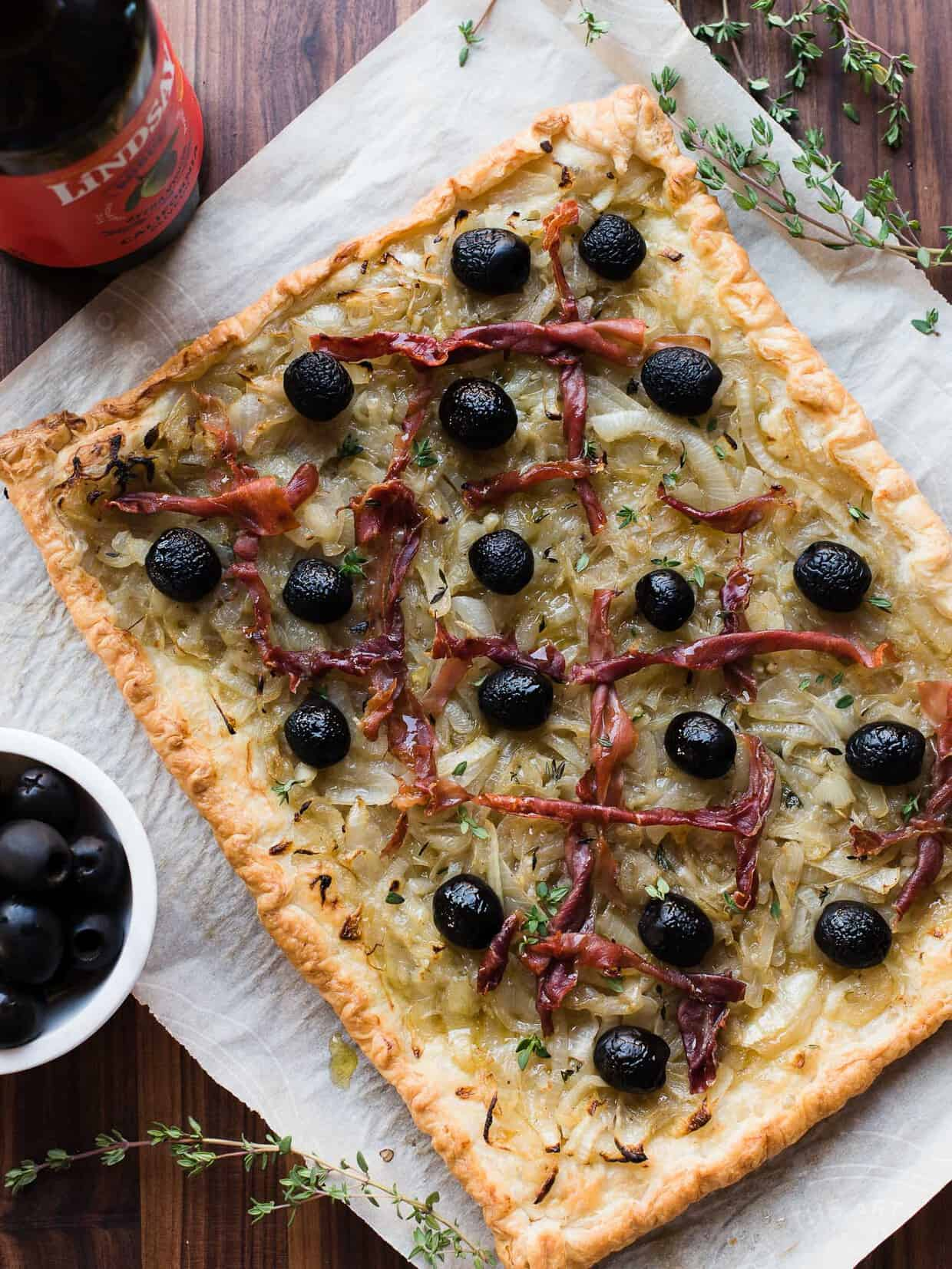 Ribbons of prosciutto on a pissaladière made with Lindsay Olives. #ad