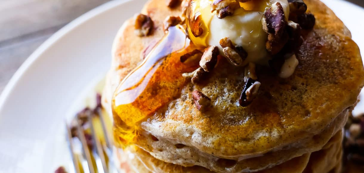 Stack of sweet potato pancakes with maple syrup pouring on top.