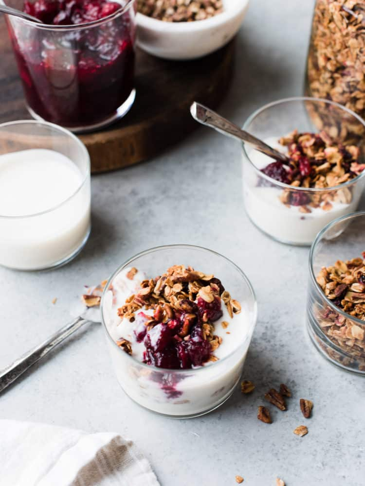 Leftover cranberry sauce granola served with yogurt in a glass.
