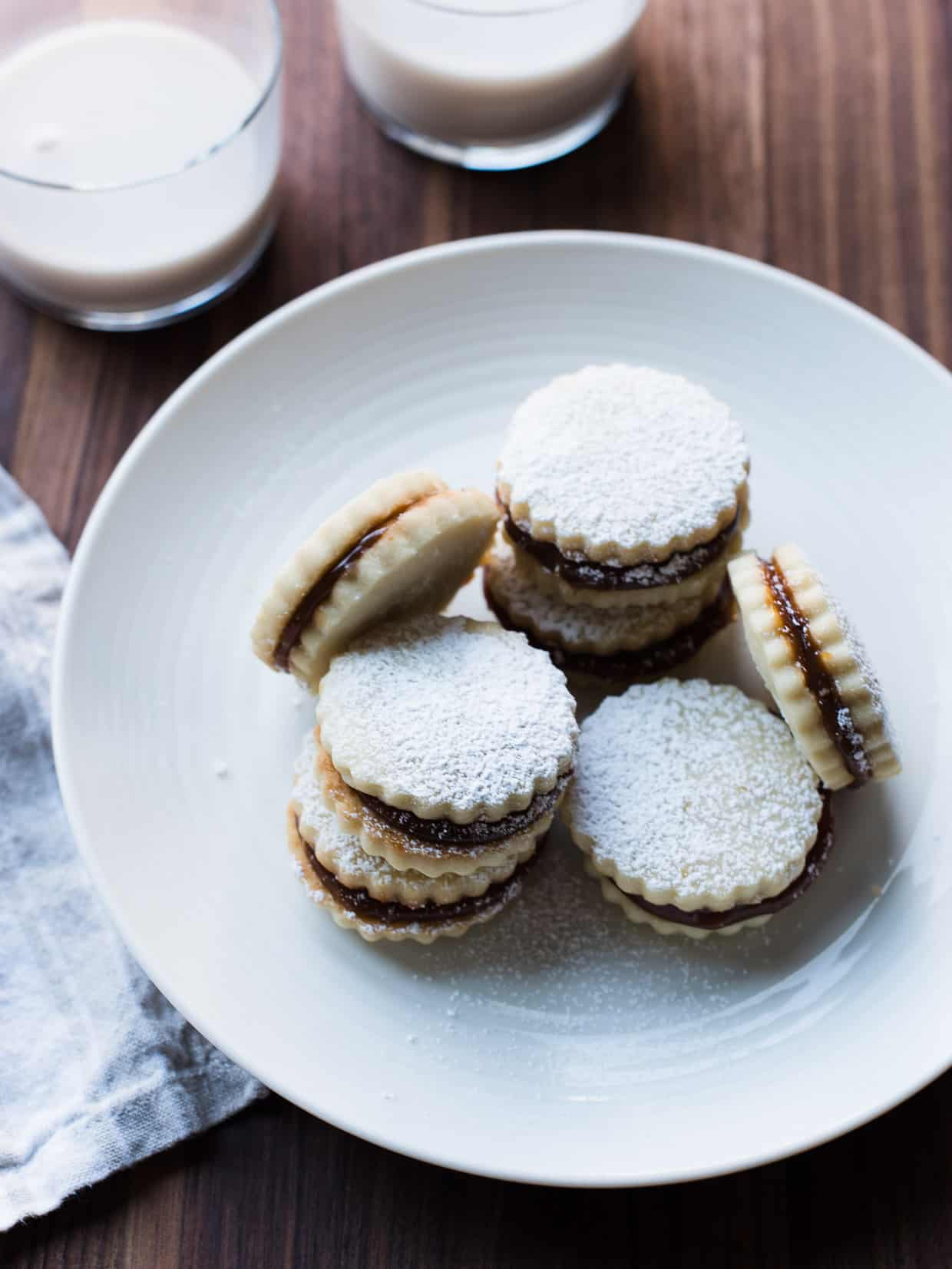 Alfajores on a white plate with two glasses of milk in the background.